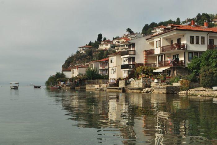I primi timidi raggi di sole baciano le case sul lago